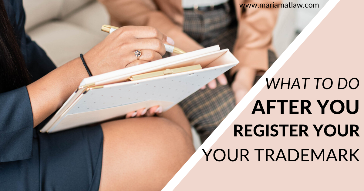 image of business women, attorney and client sitting with a notebook in hand and discussing steps to take after trademark registration