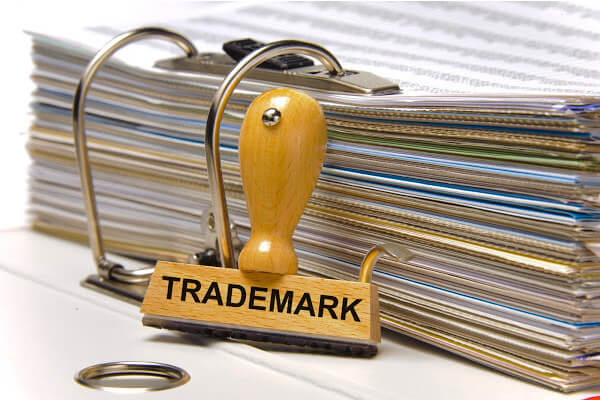 An image of a stamp with the word trademark on it next to stack of documents